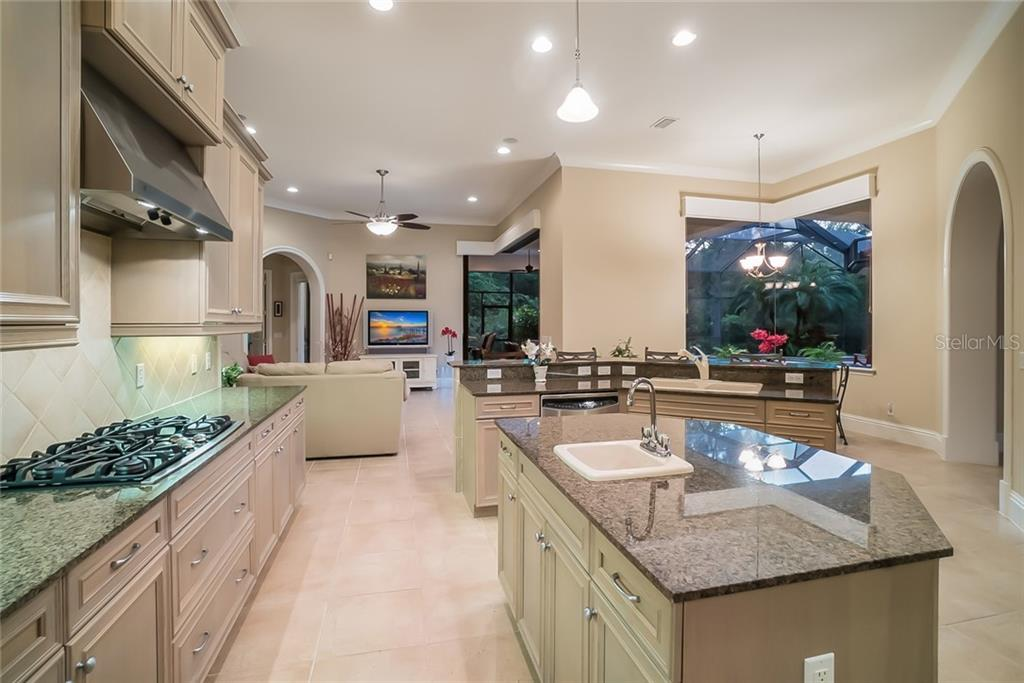 Kitchen opens to dinette and family room - and has fantastic views of the entertaining spaces, pool and preserve. - Single Family Home for sale at 13223 Palmers Creek Ter, Lakewood Ranch, FL 34202 - MLS Number is A4408290