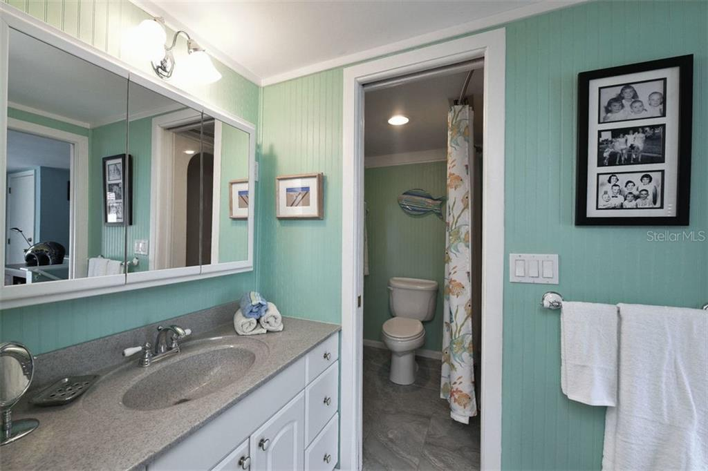En-suite bathroom off 3rd bedroom. Bead board accents, with pocket door to bath/shower and toilet. - Single Family Home for sale at 417 Bayview Pkwy, Nokomis, FL 34275 - MLS Number is A4411087