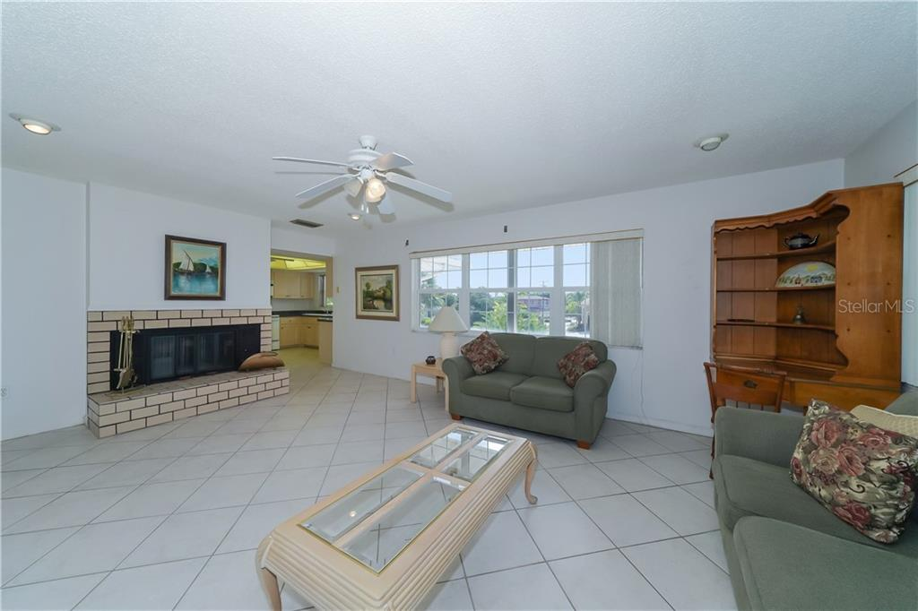 Family/great room off the kitchen.  Wood burning fireplace. - Single Family Home for sale at 5591 Cape Aqua Dr, Sarasota, FL 34242 - MLS Number is A4411099