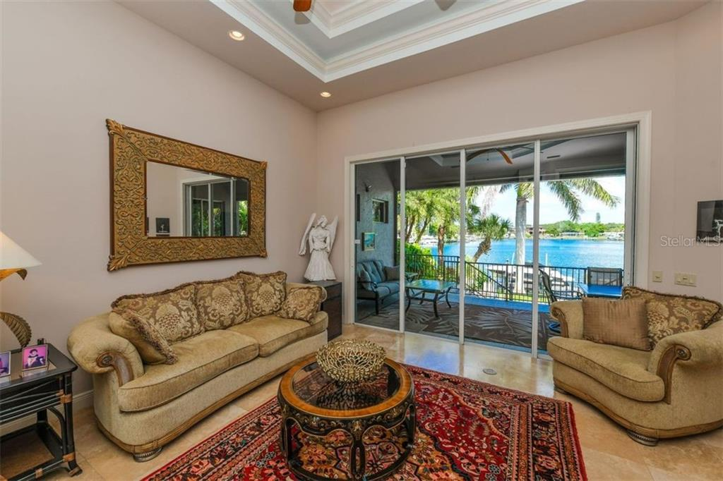 Formal living opens to lanai with remote control screen. - Single Family Home for sale at 1483 Tangier Way, Sarasota, FL 34239 - MLS Number is A4414757