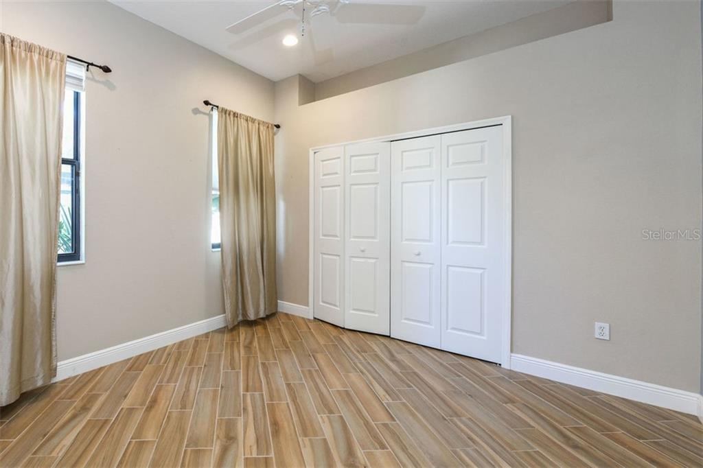 Guest Bedroom with Porcelain Plank Tile - Single Family Home for sale at 7060 Whitemarsh Cir, Lakewood Ranch, FL 34202 - MLS Number is A4417363