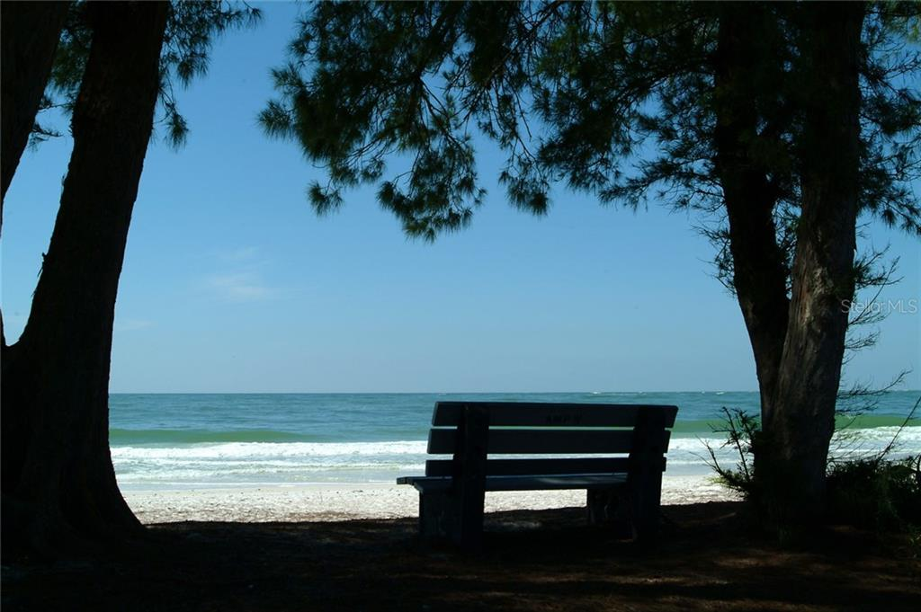 A favored bench to take in the Old Florida vibe on the Gulf of Mexico in a shady spot, just waiting for you! - Condo for sale at 600 Manatee Ave #202, Holmes Beach, FL 34217 - MLS Number is A4419465