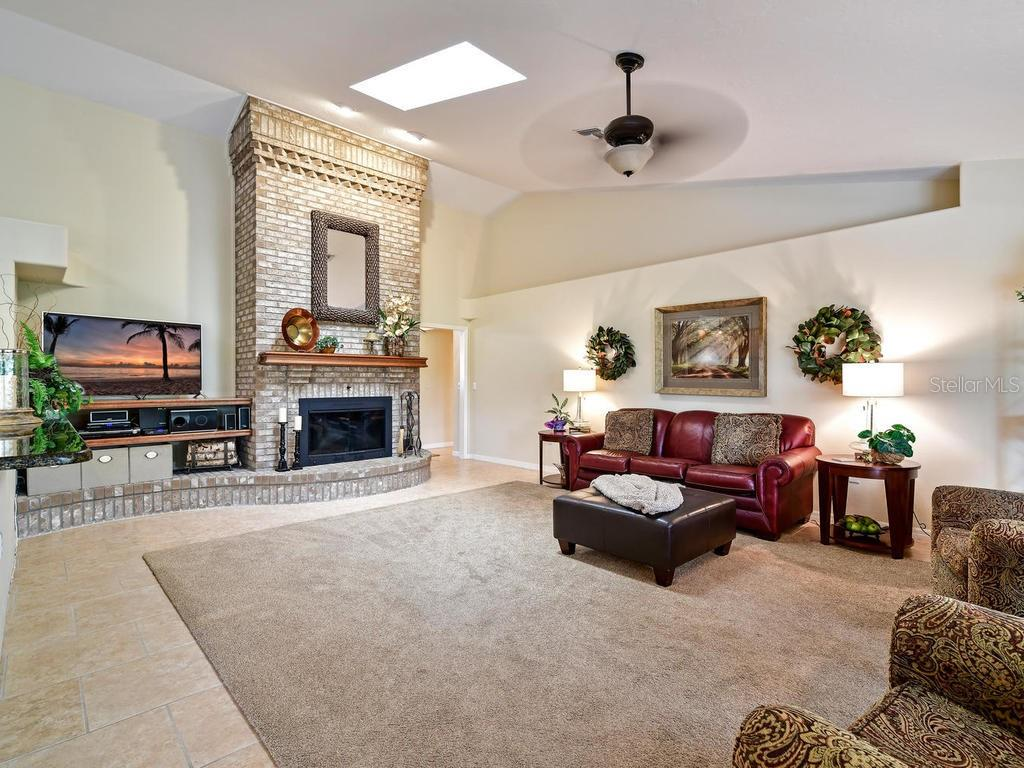 Great room with high ceilings and a floor to ceiling brick fireplace is so nice and cozy. - Single Family Home for sale at 9902 Braden Run, Bradenton, FL 34202 - MLS Number is A4419792