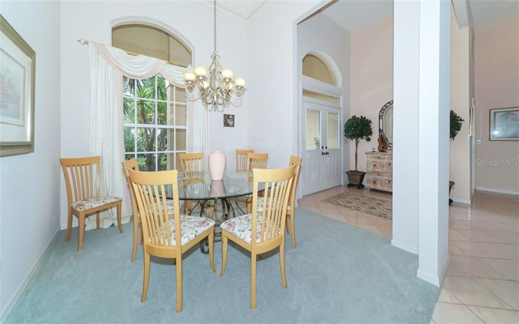 Dining room & foyer, large windows & vaulted ceilings. - Single Family Home for sale at 6125 Varedo Ct, Sarasota, FL 34243 - MLS Number is A4420656