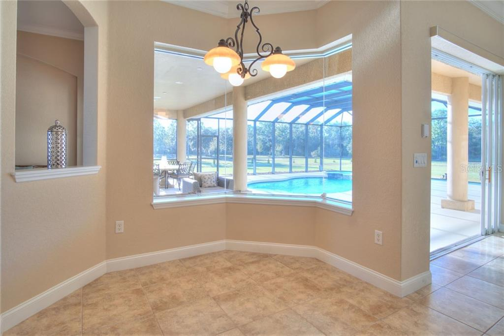 Family room with pocket sliders glass doors to pool area - Single Family Home for sale at 29425 Saddlebag Trl, Myakka City, FL 34251 - MLS Number is A4422648