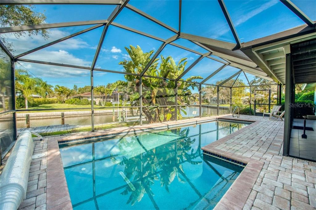 Pool view looking out to canal - Single Family Home for sale at 5548 Shadow Lawn Dr, Sarasota, FL 34242 - MLS Number is A4423461
