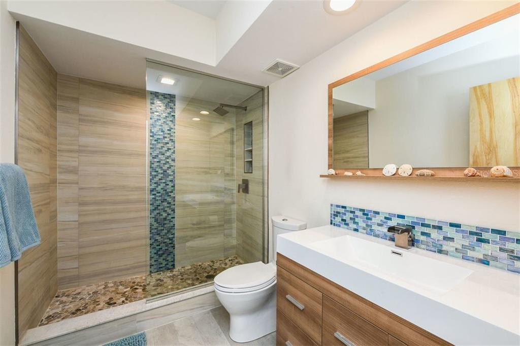 Glass enclosed shower features translucent glass tile trim, rain head shower, and Turkish marble stone shower floor.  Narrow profile Kohler toilet with European dual flush system. - Condo for sale at 225 Hourglass Way #208, Sarasota, FL 34242 - MLS Number is A4425323