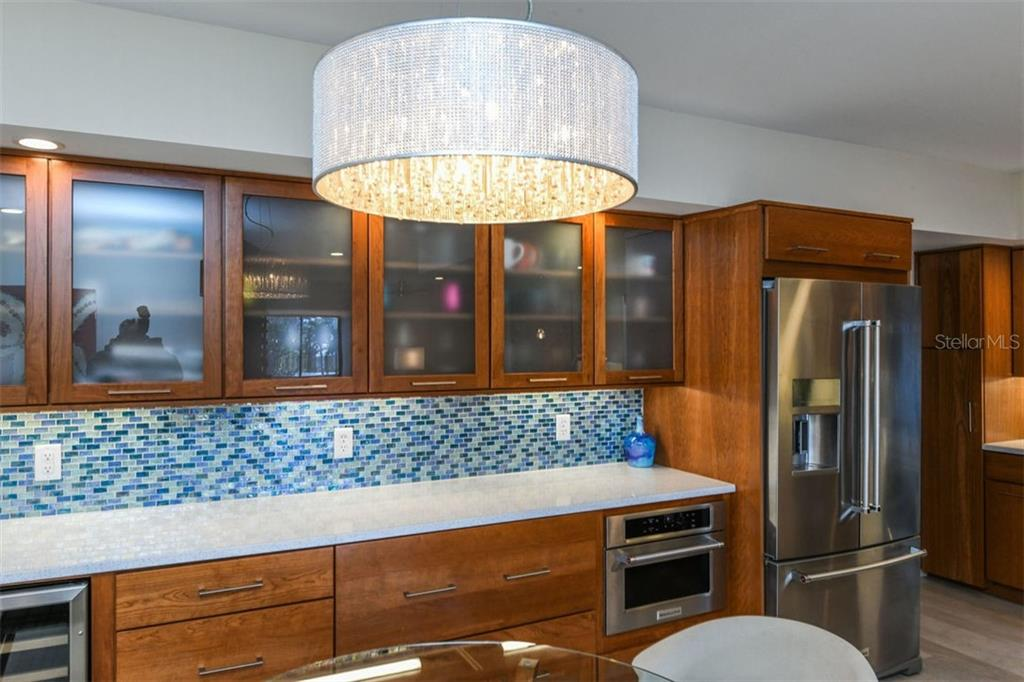Kitchen & dining room.  Built-in wine refrigerator and microwave oven. - Condo for sale at 225 Hourglass Way #208, Sarasota, FL 34242 - MLS Number is A4425323