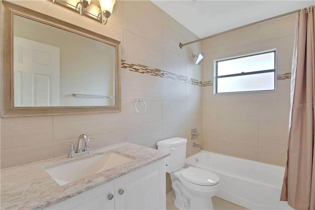 Guest Bathroom with bath tub. - Single Family Home for sale at 23265 Mcburney Ave, Port Charlotte, FL 33980 - MLS Number is A4426235