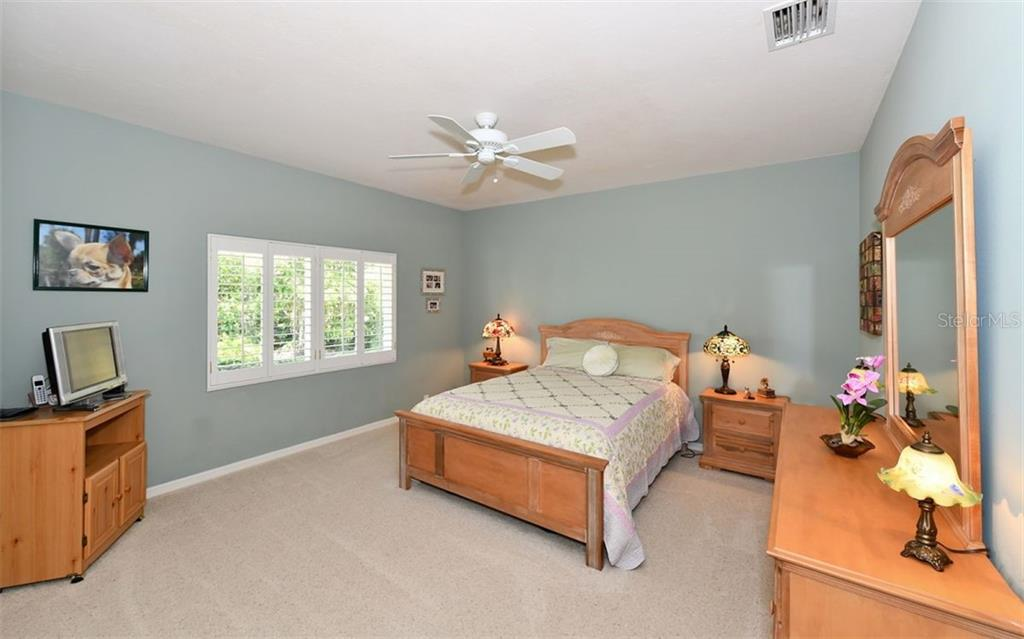Off the family room is Bedroom 2 - Single Family Home for sale at 7867 Estancia Way, Sarasota, FL 34238 - MLS Number is A4426528