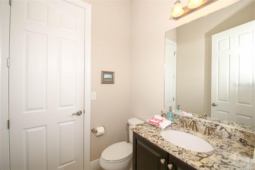 Downstairs powder room with door to storage area under staircase. - Single Family Home for sale at 5504 Tidewater Preserve Blvd, Bradenton, FL 34208 - MLS Number is A4429479