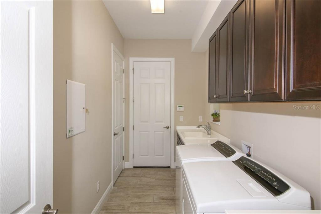 Laundry room has built in cabinetry and utility sink - Single Family Home for sale at 5504 Tidewater Preserve Blvd, Bradenton, FL 34208 - MLS Number is A4429479