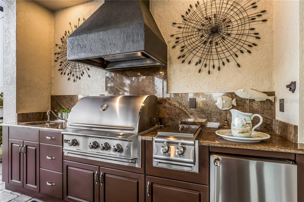 Outdoor kitchen is equipped with a beverage cooler, 2 burners, a sink and granite counter tops. - Single Family Home for sale at 19432 Newlane Pl, Bradenton, FL 34202 - MLS Number is A4432094