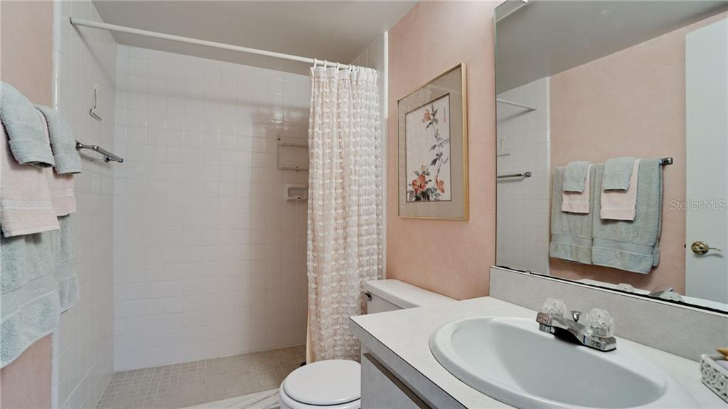 Guest, second bedroom en suite bathroom with walk in shower. - Condo for sale at 7145 Gulf Of Mexico Dr #24, Longboat Key, FL 34228 - MLS Number is A4433880