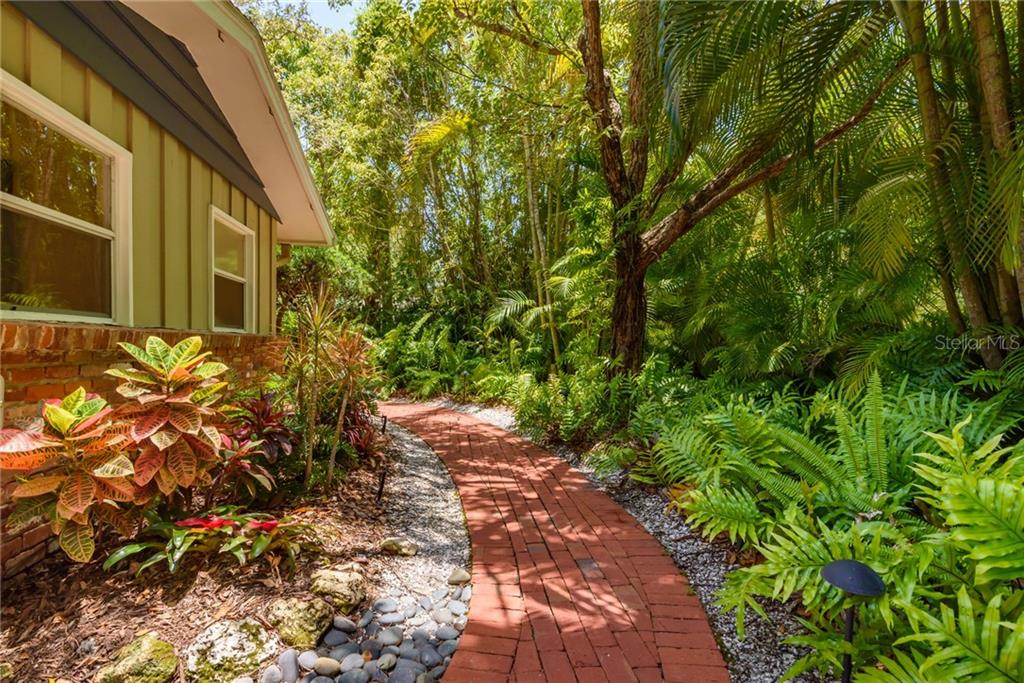Red brick walkway through the tropical gardens - Single Family Home for sale at 8511 Heron Lagoon Cir, Sarasota, FL 34242 - MLS Number is A4439489