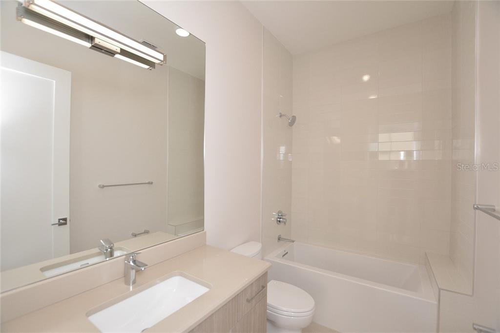Bedroom 3 en-suite bath offers a deep tub and shower combination. - Condo for sale at 609 Golden Gate Pt #202, Sarasota, FL 34236 - MLS Number is A4441802