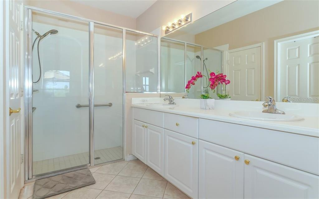 Master bathroom with dual sinks and ample storage. - Single Family Home for sale at 114 Padova Way #52, North Venice, FL 34275 - MLS Number is A4442496
