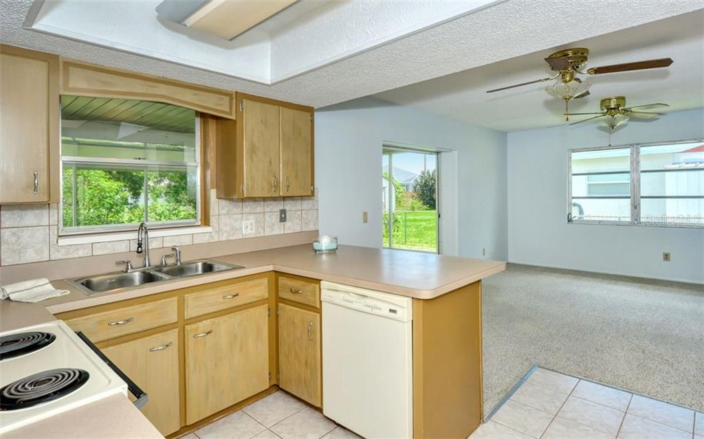 The kitchen is located near the family room and offers a pass through window access to the lanai! - Single Family Home for sale at 3286 Jamestown St, Port Charlotte, FL 33952 - MLS Number is A4444310