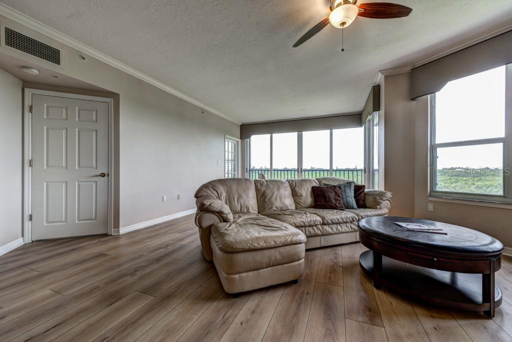A view of the great room looking southwest through the sliding glass doors and large picture windows, all of which feature interior roll down shades for privacy if desired. - Condo for sale at 5420 Eagles Point Cir #204, Sarasota, FL 34231 - MLS Number is A4454318