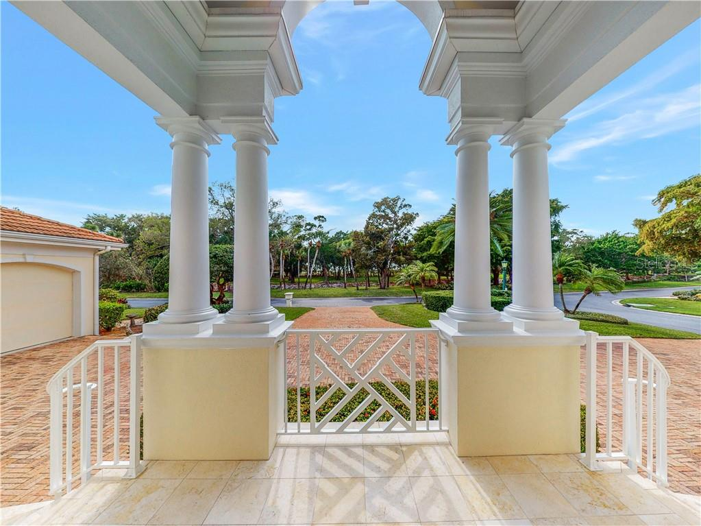 Looking westward toward the natural open green space from the lovely front entry. - Single Family Home for sale at 1590 Harbor Sound Dr, Longboat Key, FL 34228 - MLS Number is A4463437