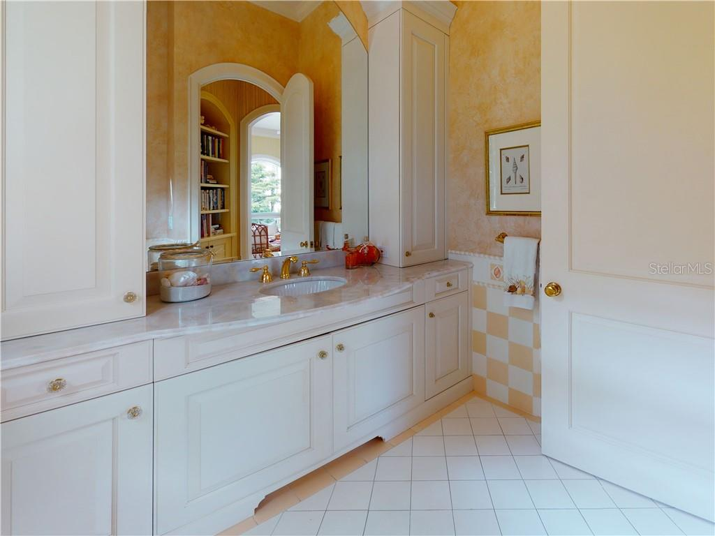 The powder room off the sunroom has nice storage for beach towels and more. - Single Family Home for sale at 1590 Harbor Sound Dr, Longboat Key, FL 34228 - MLS Number is A4463437