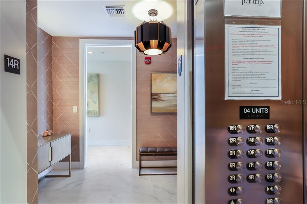 Entering your private elevator lobby, which has been customized with wallpaper and a chic light fixture - what a jewel box feel! - Condo for sale at 1155 N Gulfstream Ave #1404, Sarasota, FL 34236 - MLS Number is A4467921