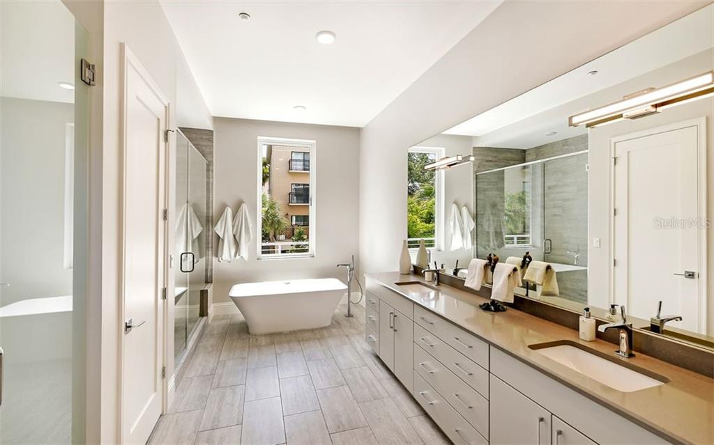 The master bath offers a deep soaking tub, expansive shower, separate water closet with beautiful porthole view,  ample dual vanity with quartz counters, and space for a linen closet. - Condo for sale at 609 Golden Gate Pt #201, Sarasota, FL 34236 - MLS Number is A4468917