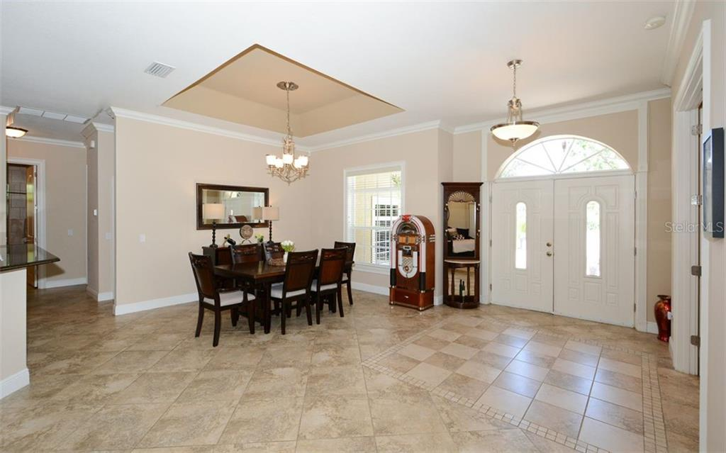 View from formal living room back to double glass front doors and formal dining space - Single Family Home for sale at 1623 Jacana Ct, Nokomis, FL 34275 - MLS Number is A4470679