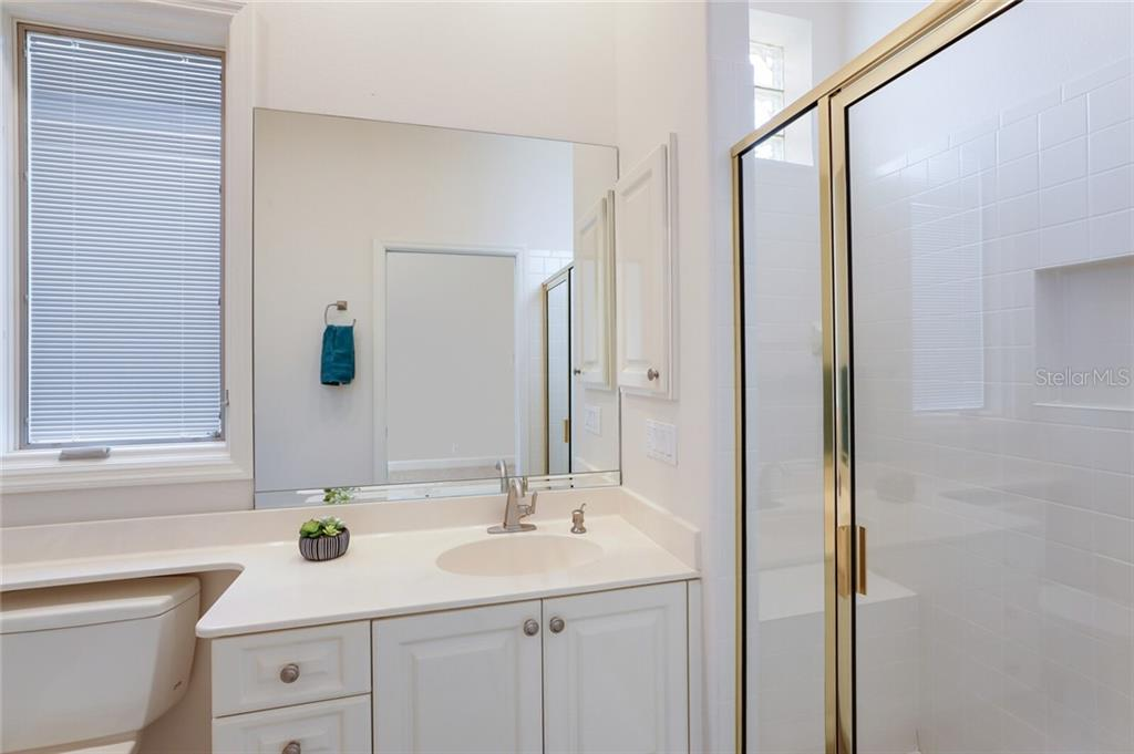 This en-suite guest bath was an upgrade during the building process and includes a lavish walk-in shower and large vanity. - Single Family Home for sale at 9618 53rd Dr E, Bradenton, FL 34211 - MLS Number is A4477826