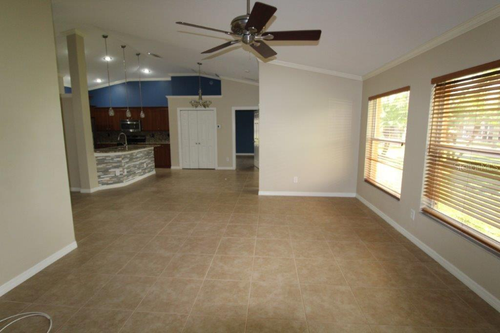 6358 Sturbridge Ct. Living Room and Dining Room Open Plan, all Tile Floor, Cathedral Ceiling, Windows Overlooking Lake View - Single Family Home for sale at 6358 Sturbridge Ct, Sarasota, FL 34238 - MLS Number is A4480857