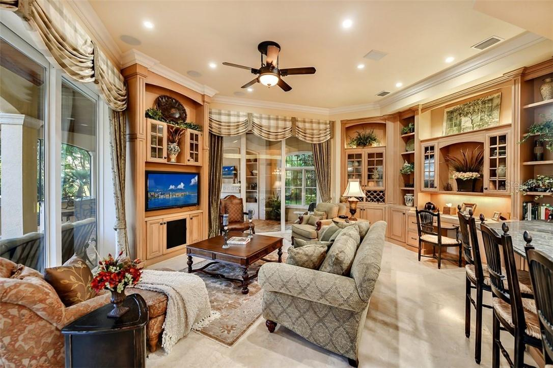 The Family room off the eat in kitchen, built in desk area w/ loads of shelving & built ins, both sliders open up to the pool/spa & BBQ - outdoor kitchen area - Single Family Home for sale at 8263 Archers Ct, Sarasota, FL 34240 - MLS Number is A4483993