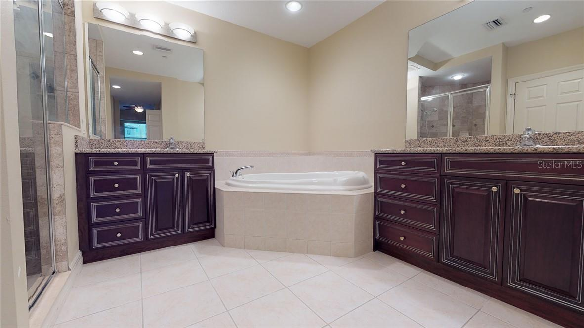 Primary bathroom with garden tub and cherry wood finishes - Condo for sale at 5591 Cannes Cir #506, Sarasota, FL 34231 - MLS Number is A4484243