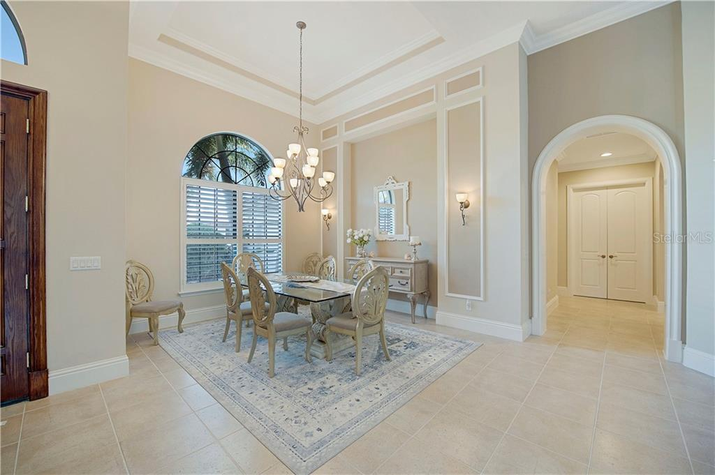 Formal dining room with tray ceiling and architectural details framed with wall sconces - Single Family Home for sale at 13223 Palmers Creek Ter, Lakewood Ranch, FL 34202 - MLS Number is A4484826