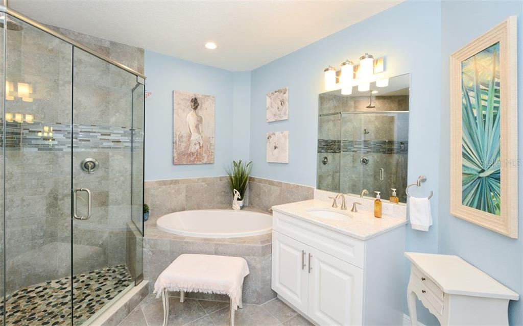 Master bath with tub, shower & dual vanities. - Condo for sale at 7730 34th Ave W #102, Bradenton, FL 34209 - MLS Number is A4486333
