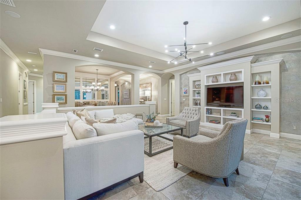 Family room with tray ceiling, recessed lights, and built -in cabinetry - Single Family Home for sale at 14725 Secret Harbor Pl, Lakewood Ranch, FL 34202 - MLS Number is A4491203