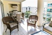 Unit E 406 has a sunny lanai with outdoor kitchen, faces the courtyard pool and has a peek-a-boo view of the Gulf! - Condo for sale at 6512 Midnight Pass Rd #406, Sarasota, FL 34242 - MLS Number is A4171720