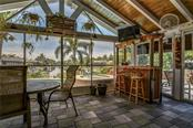 Family room opens to tropical setting with long view down canal and covered lanai with vinyl sliders, and Tiki Bar. - Single Family Home for sale at 8916 44th Avenue Dr W, Bradenton, FL 34210 - MLS Number is A4186449