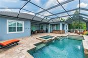 Custom designed pool with Pebble-Tech and double fountain features, sun shelf and spa located on the near side of the pool for easy access to the home. - Single Family Home for sale at 595 Fore Dr, Bradenton, FL 34208 - MLS Number is A4428657