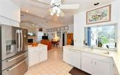 Open kitchen with pass through to covered lanai and pool and spa;  Pool and spa are caged; lanai is covered room for any weather enjoyment! - Single Family Home for sale at 5401 Downham Meadows, Sarasota, FL 34235 - MLS Number is A4436577