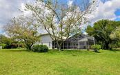 rear elevation of home....trees will be in full bloom to complete the lush landscape! - Single Family Home for sale at 5401 Downham Meadows, Sarasota, FL 34235 - MLS Number is A4436577