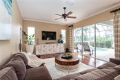 Family room with wood floors, sliders out to pool deck and views of lake - Single Family Home for sale at 13818 Nighthawk Ter, Lakewood Ranch, FL 34202 - MLS Number is A4438487