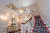 Beautiful wood staircase wrapping around chandelier with a landing at double glass panel doors that lead to an open balcony overlooking the front gardens. - Single Family Home for sale at 3702 Beneva Oaks Blvd, Sarasota, FL 34238 - MLS Number is A4438878