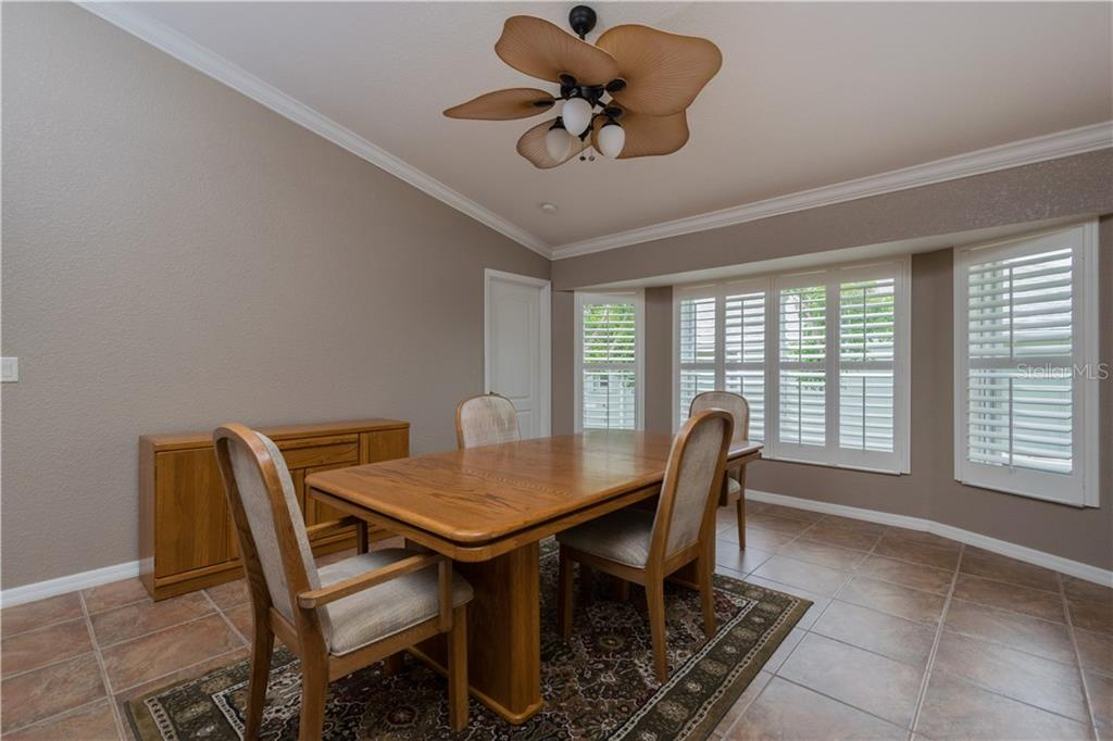 Family Room currently used as a Formal Dining area, Crown Molding, Vaulted Ceiling, Bahama Shutters. - Single Family Home for sale at 5149 Latham Ter, Port Charlotte, FL 33981 - MLS Number is N5914515