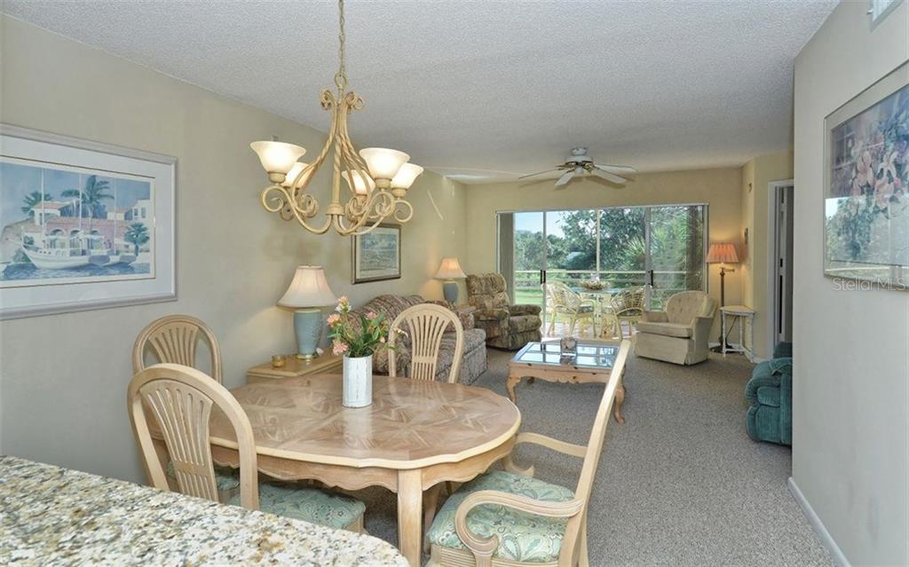 Dining room, living room to lanai - Condo for sale at 1036 Wexford Blvd #1036, Venice, FL 34293 - MLS Number is N5915474