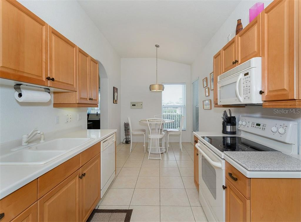 Kitchen to breakfast nook - Villa for sale at 900 Onager Ct, Englewood, FL 34223 - MLS Number is N5915910