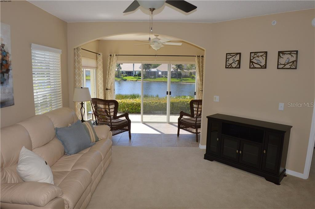 Living room to lanai with lake view - Condo for sale at 903 Addington Ct #102, Venice, FL 34293 - MLS Number is N5916962