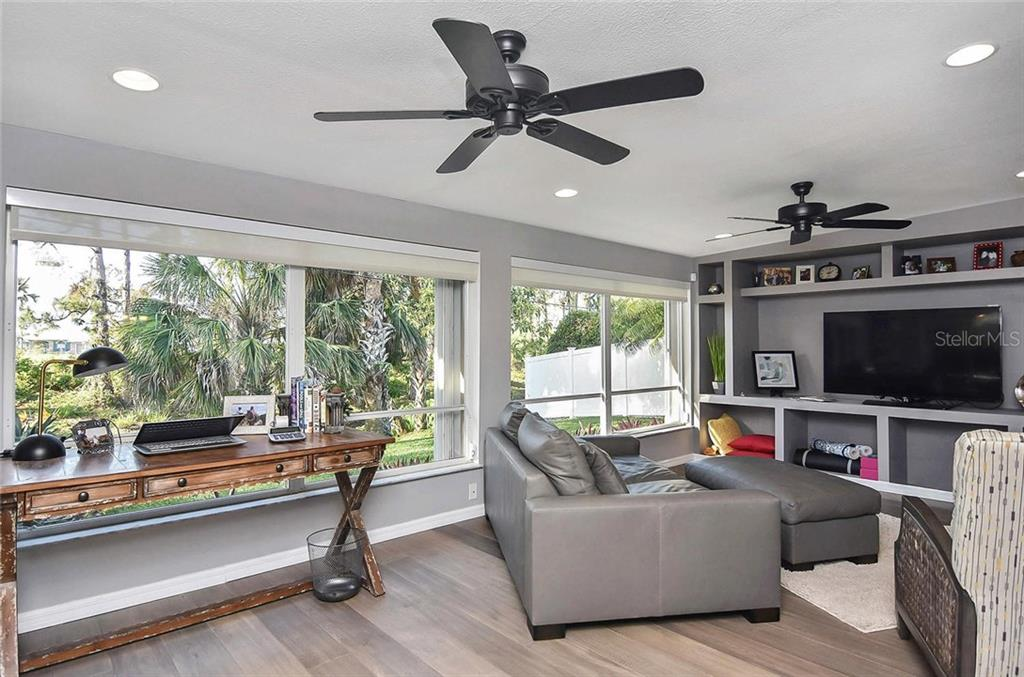 Family room with built in shelving and private views of greenery. - Single Family Home for sale at 405 Sunset Dr, Venice, FL 34285 - MLS Number is N5917234