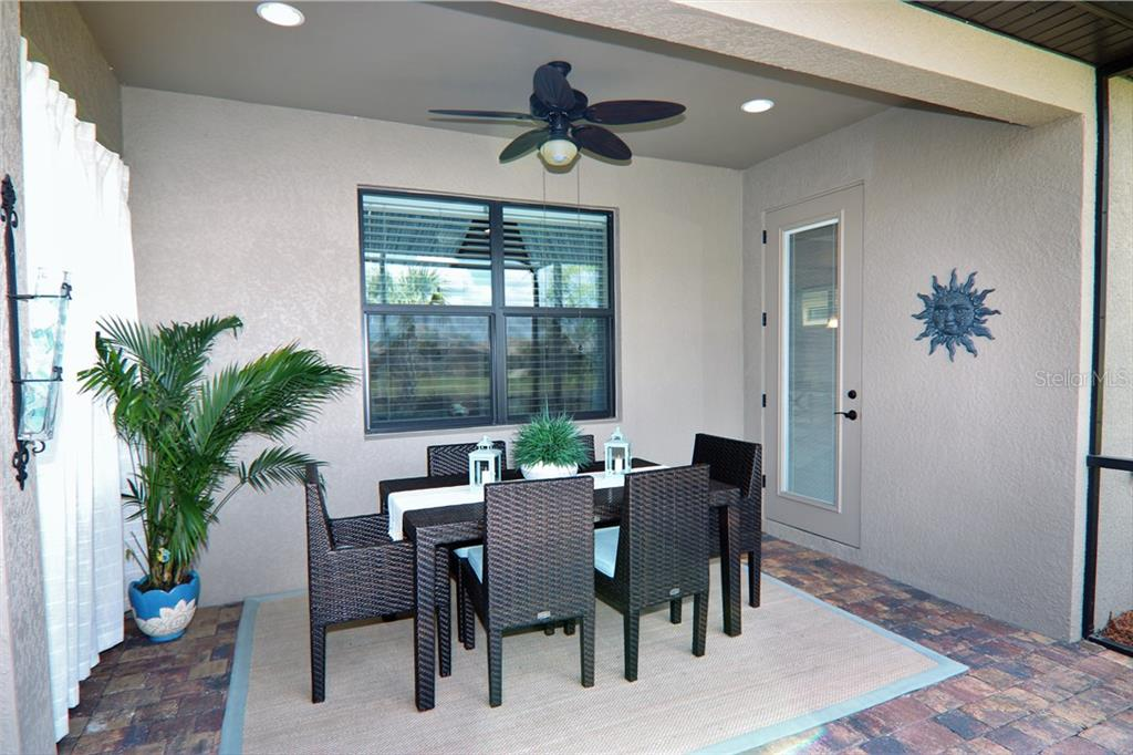 Outdoor covered lanai with brick pavers and ceiling fan - Single Family Home for sale at 13880 Lido St, Venice, FL 34293 - MLS Number is N5917319