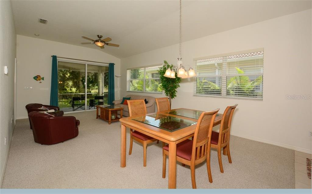 Dining area, great room with sliders to lanai - Villa for sale at 313 Auburn Woods Cir, Venice, FL 34292 - MLS Number is N6101432