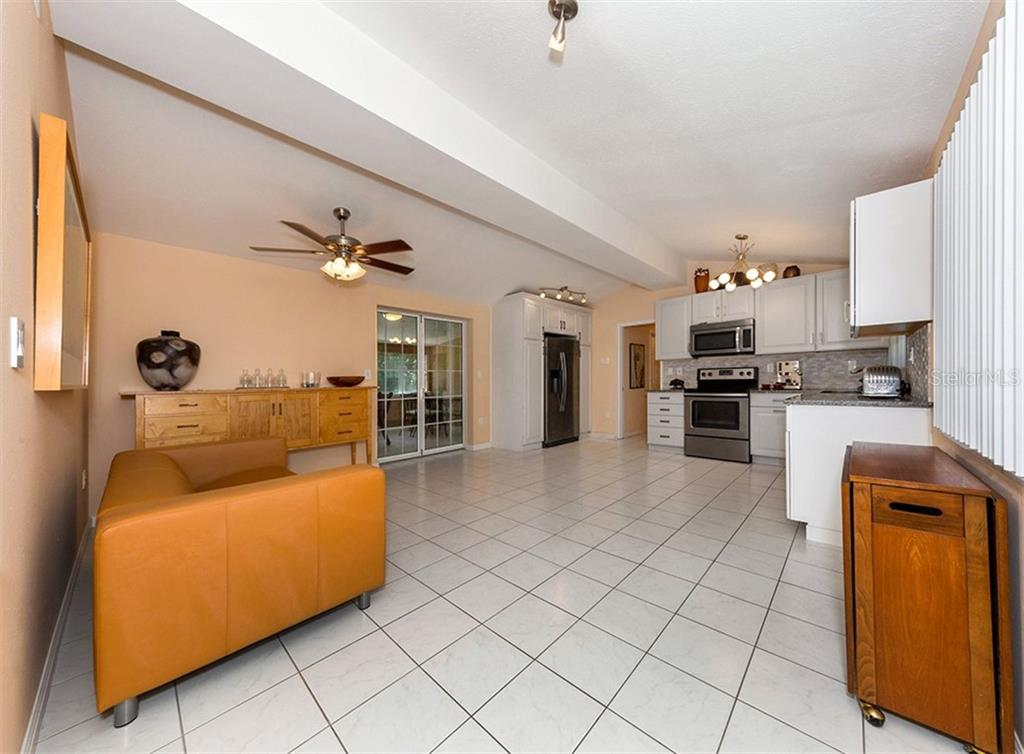 Living room, kitchen - Single Family Home for sale at 717 Guild Dr, Venice, FL 34285 - MLS Number is N6103134
